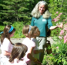 An instructor showing a blooming plant to a group of         children in the garden
